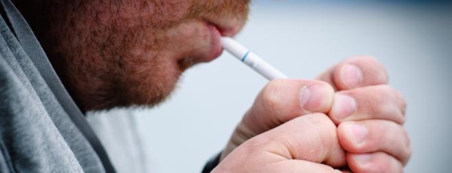 Mann, der sich Zigarette anzündet.