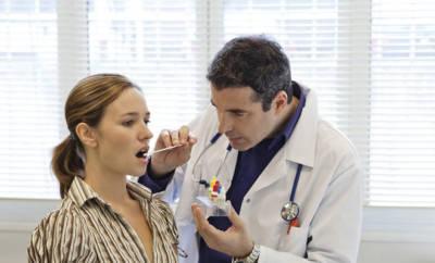 Arzt untersucht Rachen einen