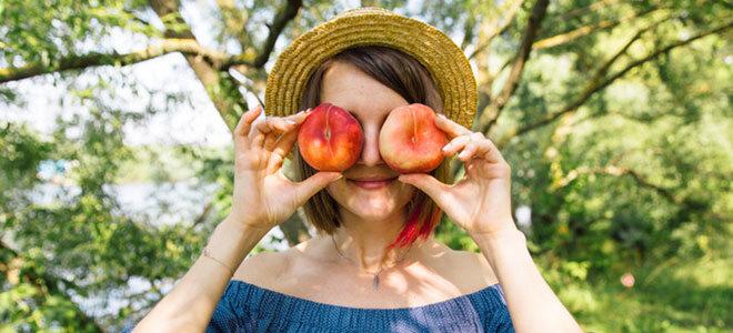 Eine junge Frau hält sich scherzhaft zwei Pfirsiche vor die Augen.