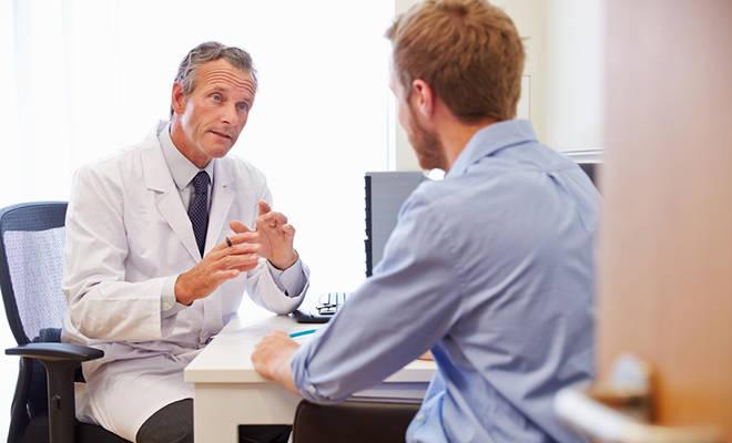 Junger Mann im Gespräch mit Arzt.