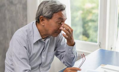 Älterer Mann, der sich angestrengt die Augen reibt.