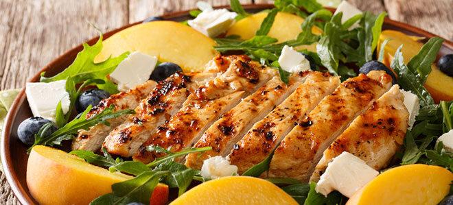 Ein Salat mit gegrillter Hähnchenbrust, Pfirsichscheiben, Rucola, Heidelbeeren und Feta.