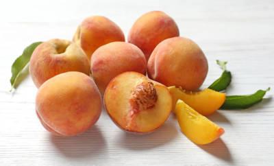Eine Handvoll Pfirsiche auf hellem Holzgrund.