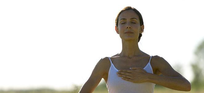 Frau, die mit Hand auf der Brust einatmet.