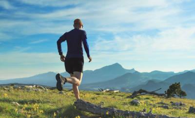 Ein Mann um die 40 läuft über eine Bergwiese.