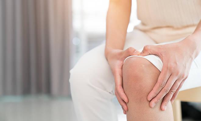 Ausschnitt Frau fasst sich ans Knie.