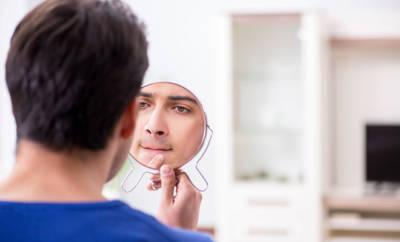 Mann mit Mitesser vor einem Spiegel