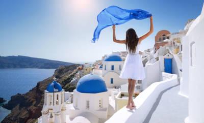 Eine junge Frau mit blauem Tuch spaziert über ein Mauerwerk auf der Insel Santorin.
