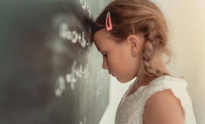 Kleines Mädchen, dass sich frustriert an die Tafel lehnt.