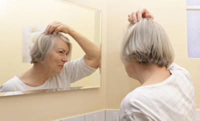 Seniorin, die im Spiegel ihre Haare betrachtet.