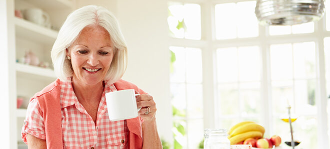 Seniorin die eine Tasse Tee trinkt.