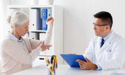 Seniorin zeigt Arzt Gipsarm.