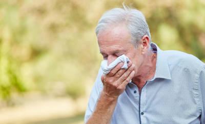 Senior, der sich die Nase schnäuzt.