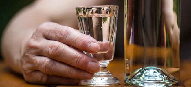 Shot-Glas mit Alkohol neben Bierglas.