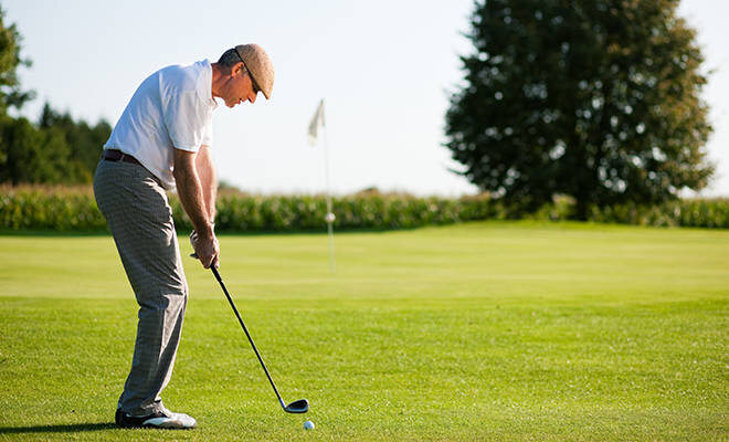 Senior beim Golf spielen
