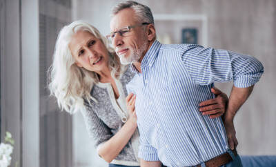 Senior greift sich mit besorgtem Gesicht an den Rücken, seine Frau steht daneben.