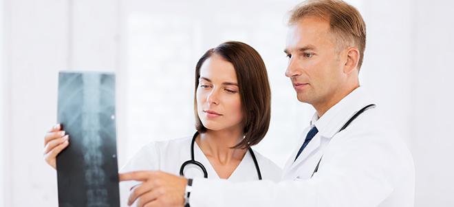 Zwei Ärzte, die ein Röntgenbild einer Wirbelsäule betrachten.