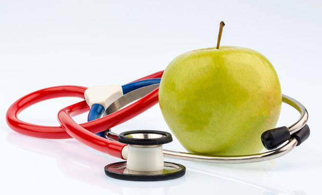 Ein grüner Apfel neben einem Stethoskop.