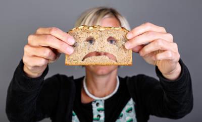 Frau hält Brot vor Gesicht, in das Grimasse geschnitten ist.