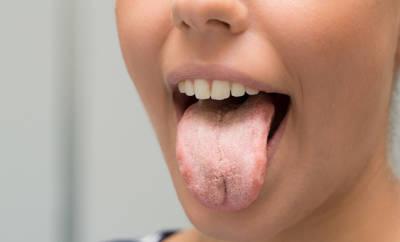 Frau, die Zunge mit Pilz raus streckt.