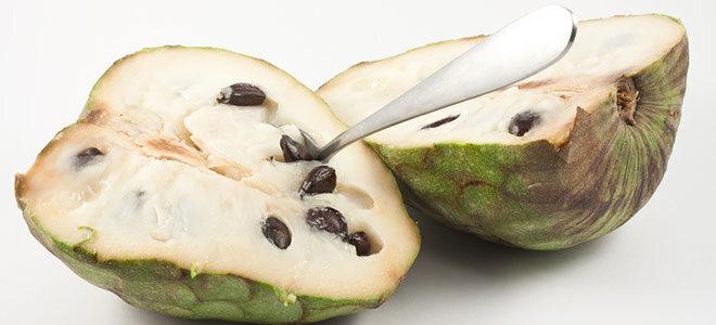 Eine halbierte Cherimoya Frucht, die mit dem Löffel gegessen werden kann.
