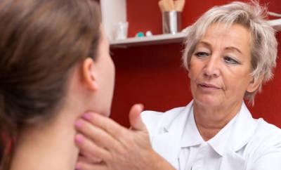 Ärztin tastet Lymphknoten am Hals einer Frau ab.
