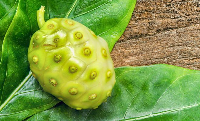 Noni-Frucht auf Holzhintergrund.