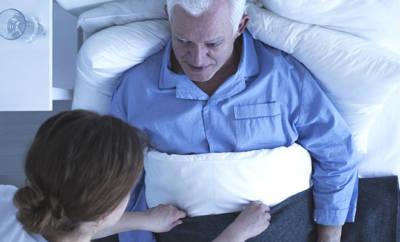 Ein älterer, sympathisch wirkender Herr wird von einer Pflegerin zugedeckt.