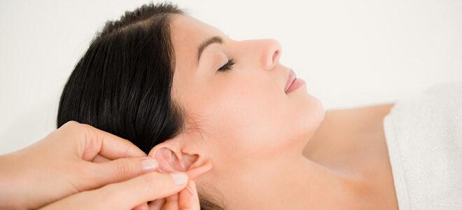 Akupunktur am Ohr mit Daumen und Zeigefinger.