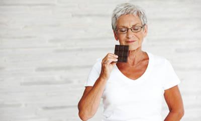 Ältere Frau mit Stück Schokolade in der Hand auf das sie schielt.