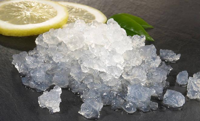 Wasserkefir-Kristalle neben Zitronenscheibe.