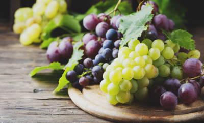 Rote, blaue und grüne Weintrauben auf einem Holzteller.