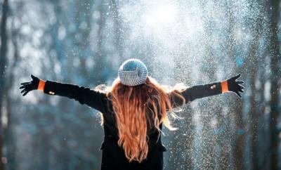 Eine junge Frau wirft Schnee in die Luft.