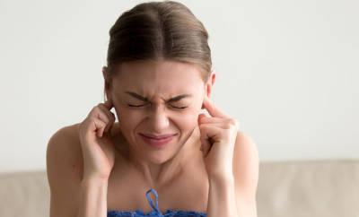 Eine Frau hält sich die schmerzenden Ohren zu.