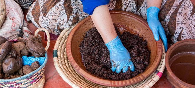 Eine Frau knetet Öl aus Argansamen.