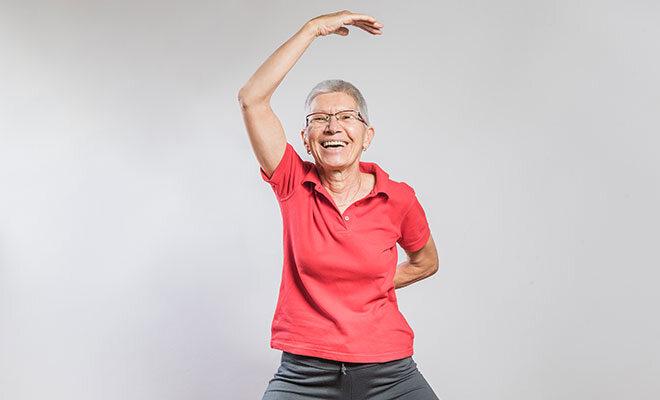 Eine Senioren bei einer Dehnübung der Schulter und Arme.