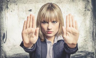 Eine Frau hält mit ihren Händen etwas ab.