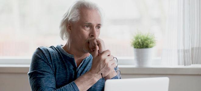 Ein besorgter Mann sitzt vor einem Laptop.