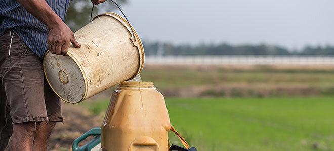 Ein Bauer füllt Wasser in einen Tank, dritte-Welt-Land.