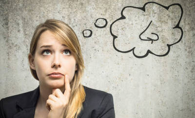 Eine junge blonde Frau mit grübelndem Blick, darüber eine gezeichnete Gedankenblase mit einer Nase