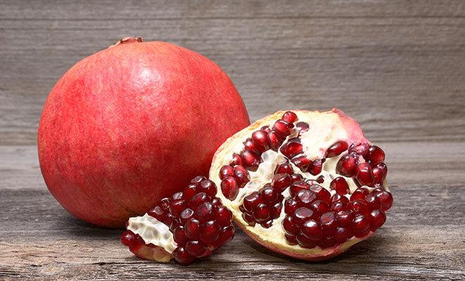 Ein ganzer roter Granatapfel, daneben liegt eine Granatapfelhäfte, bei der die roten Kerne gut zu erkennen sind.