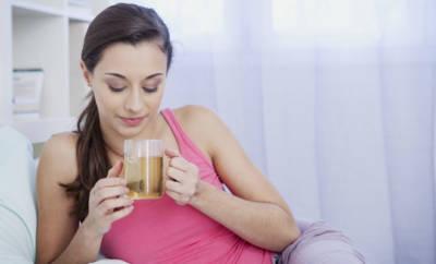Eine junge Frau trinkt ein Glas Kräutertee, um ihr Sodbrennen zu lindern.