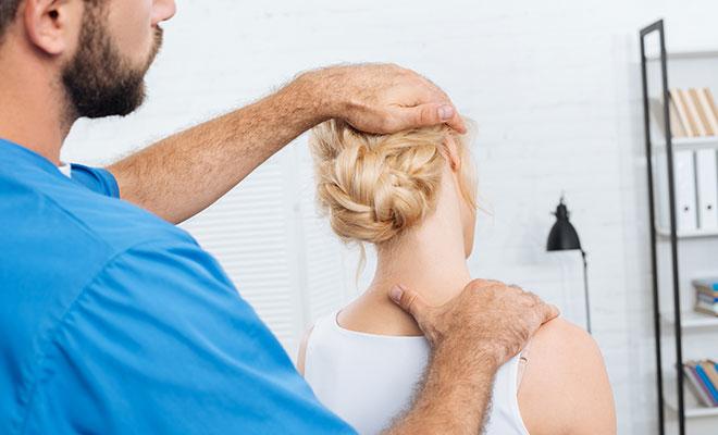 Ein Chiropraktiker behandelt den Nacken einer blonden Patientin.