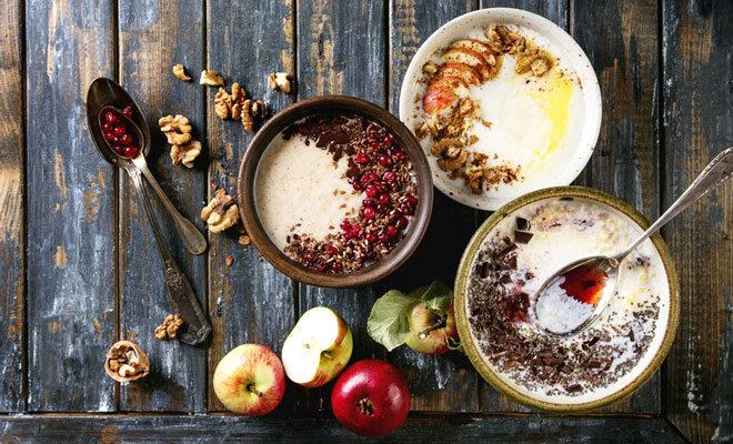 Auf einem Holztisch stehen drei Müslischälchen mit Porridge und verschiedenen Toppings, zum Beispiel Äpfel, Walnüsse und Granatapfelkerne.