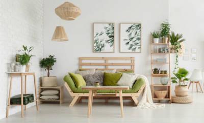 Ein hell eingerichtetes Wohnzimmer mit vielen Zimmerpflanzen, die die Luft erfrischen.