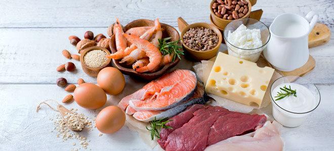Auf einem weißen Tisch liegen Lebensmittel, die essentielle Aminosäuren enthalten: Hülsenfrüchte, Haferflocken, Milchprodukte, Nüsse, Fleisch, Fisch und Eier.