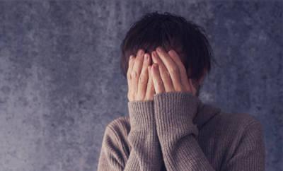 Ein junger Mann, der die Hände vor den Kopf hält und weint. Er leidet an einer anhaltenden Trauerstörung.