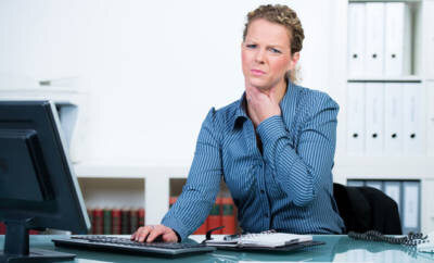 Eine Frau sitzt an ihrem Arbeitsplatz und hält ihre linke Hand an ihren Hals. Sie leidet an Heiserkeit und Stimmlosigkeit.