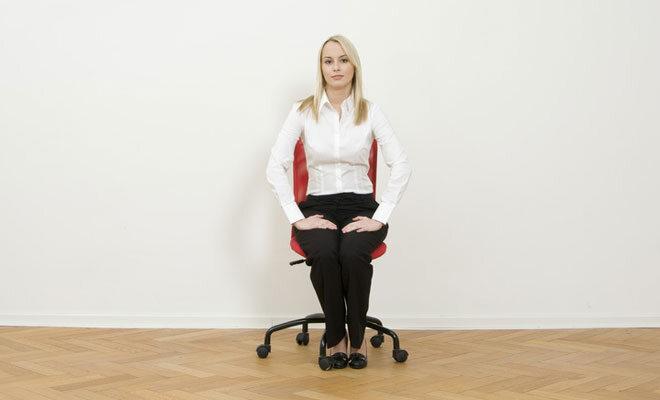 Eine junge blonde Frau sitzt aufrecht auf einem Bürostuhl.