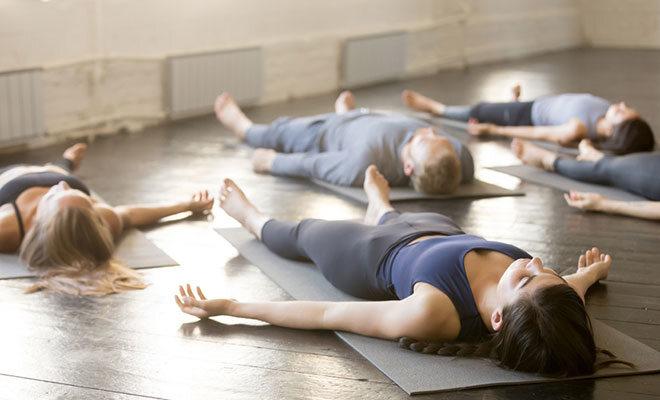 Eine Gymnastikgruppe liegt auf Yogamatten am Boden